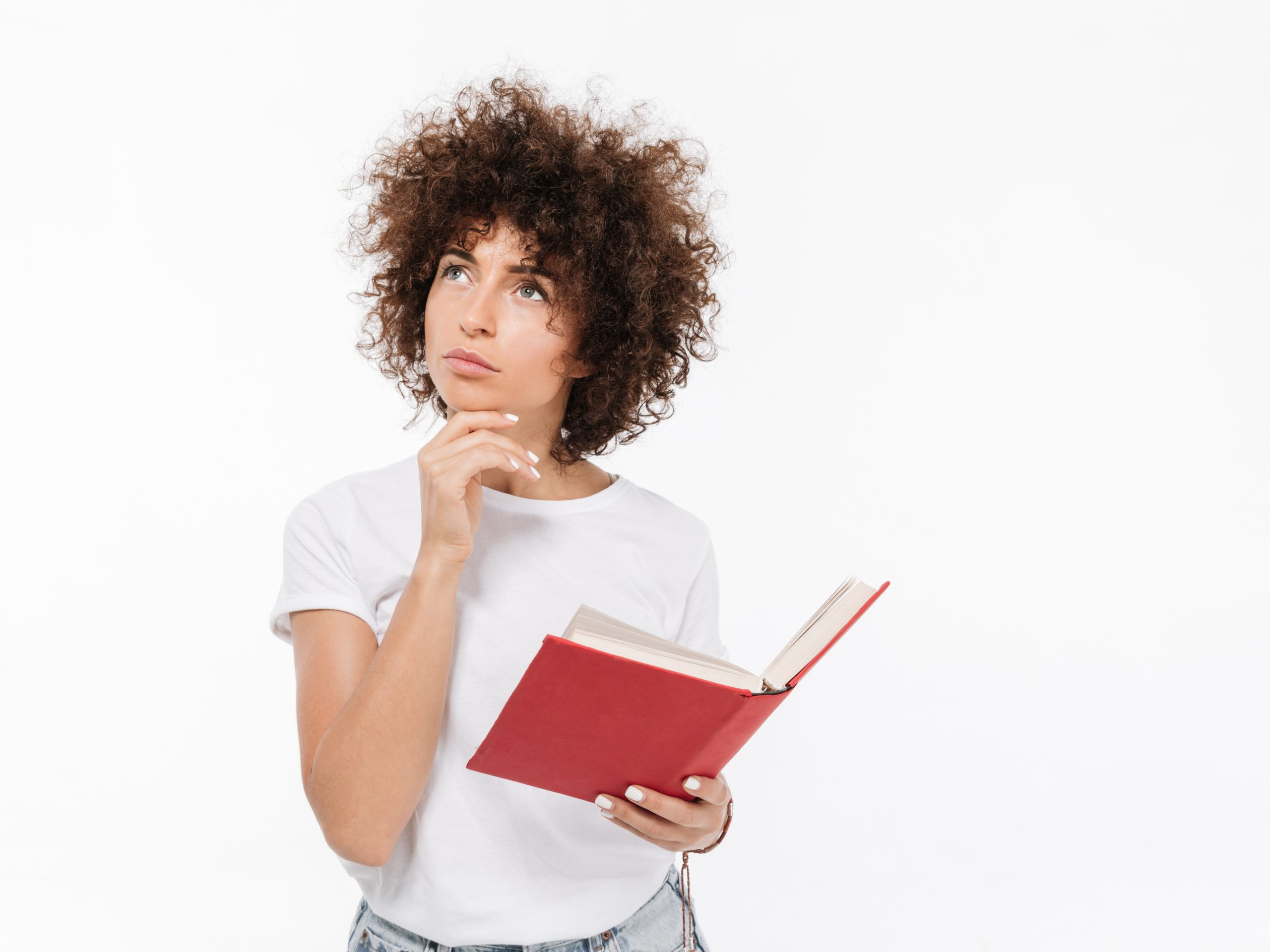 Pensive young woman holding book and looking away